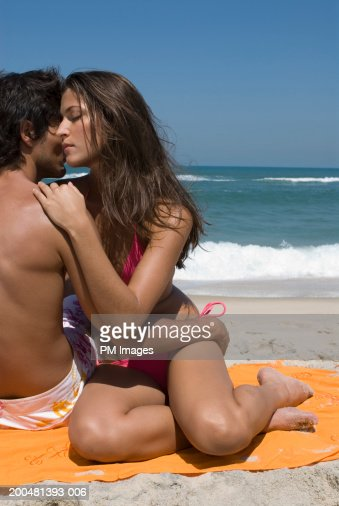 Young couple embracing at beach : ストックフォト
