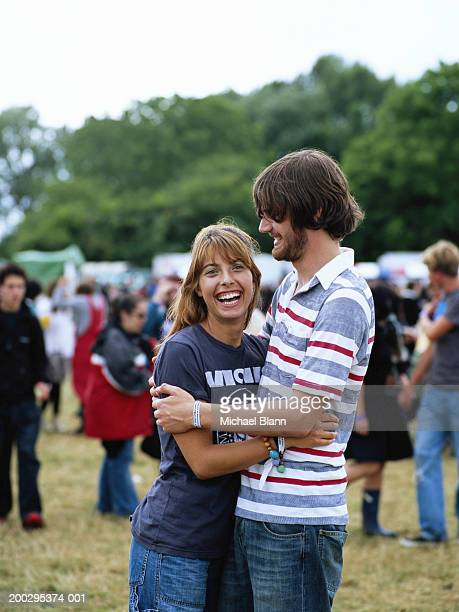 Young couple embracing at festival, woman laughing, portrait