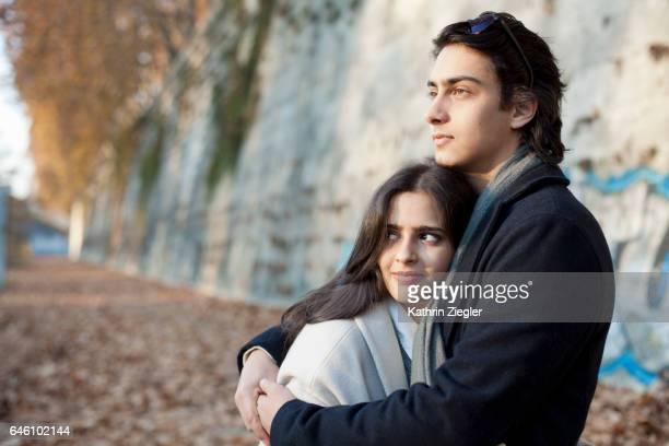 Young couple embracing at riverbank of the Tiber river, Rome, Italy