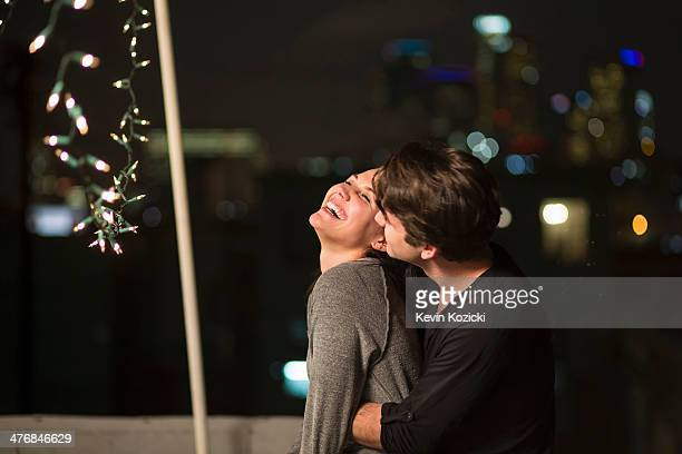 Young couple embracing at rooftop party