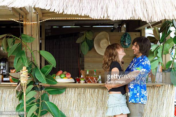 Young couple embracing by beach bar, laughing, side view