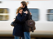 Young couple embracing each other at a railroad station platform