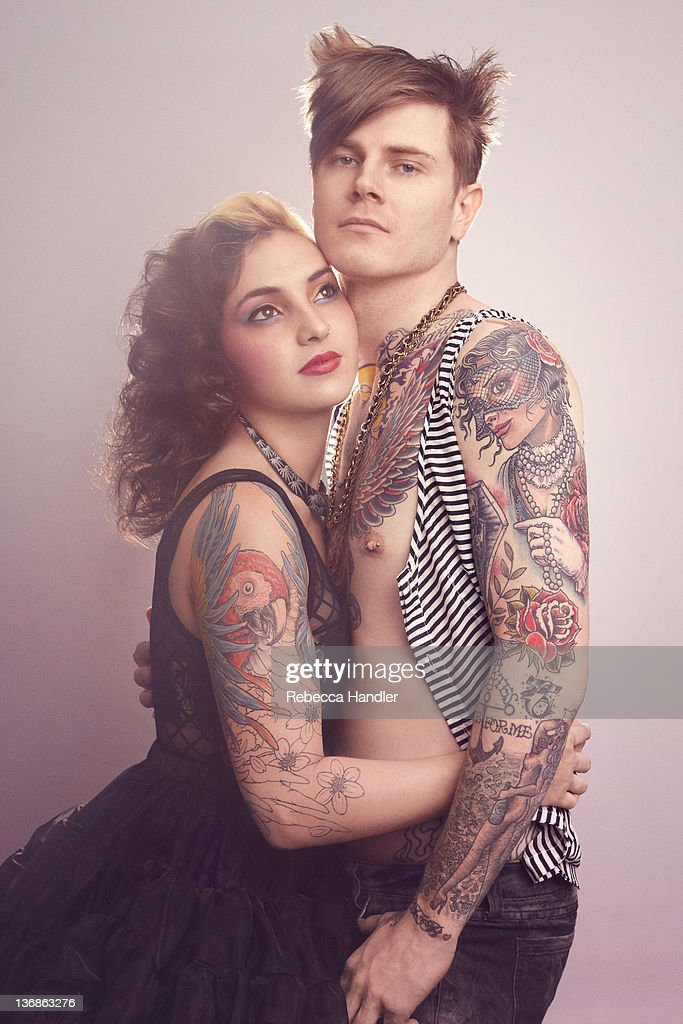 Young couple embracing in 1980s attire. : Stock Photo