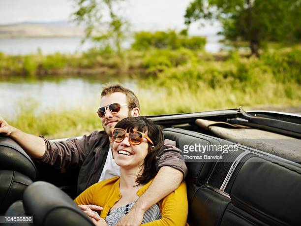 Young couple embracing in backseat of convertible