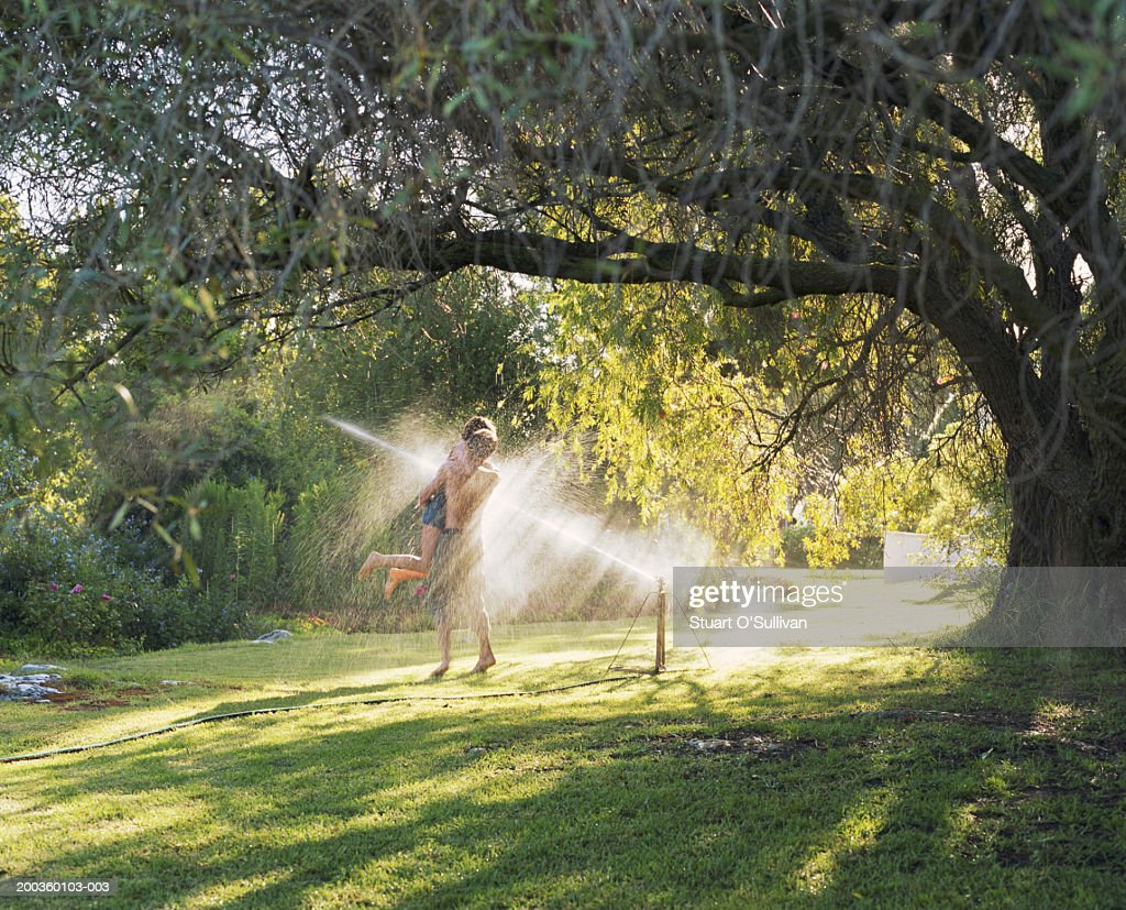 Young couple embracing in garden sprinkler