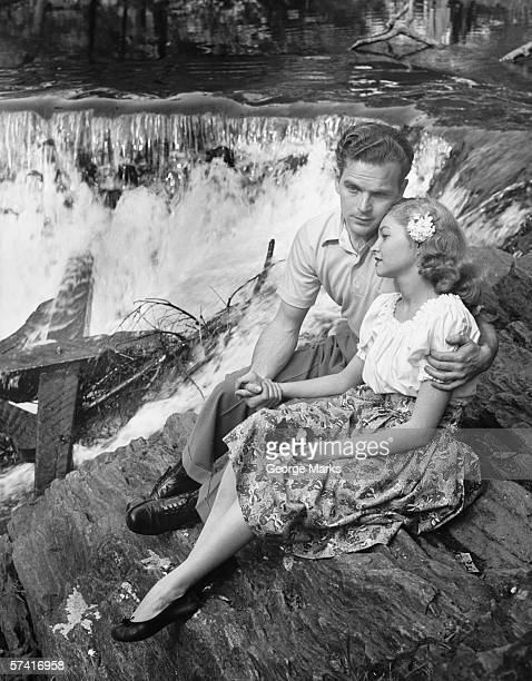 Young couple embracing near waterfall, (B&W)