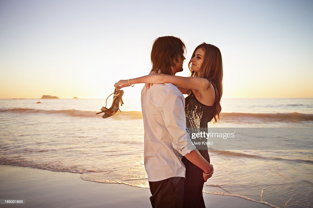 Young couple embracing on beach : Stock Photo