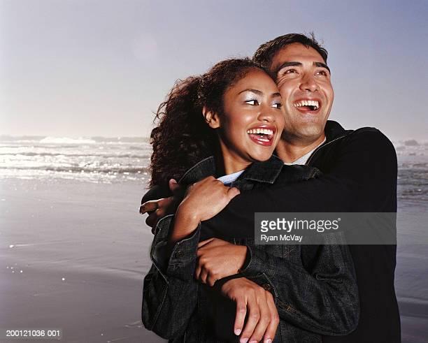 若いカップルはビーチ、笑顔を行う