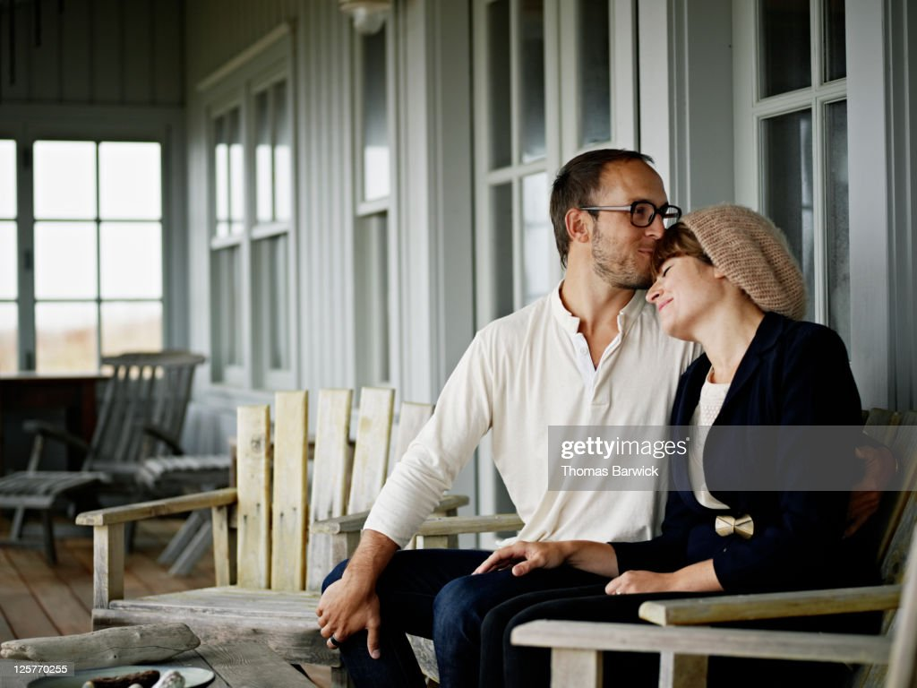Young couple embracing on front porch of home : Stock Photo