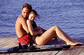 Young couple embracing on jetty, full length
