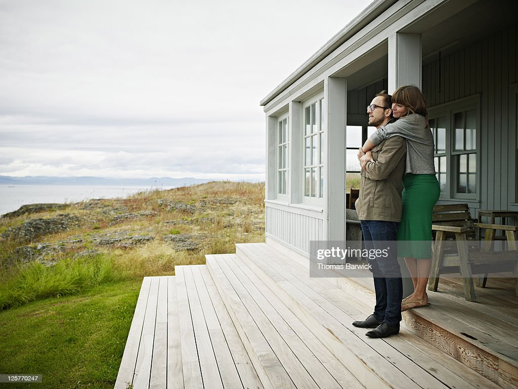 Young couple embracing on porch of home