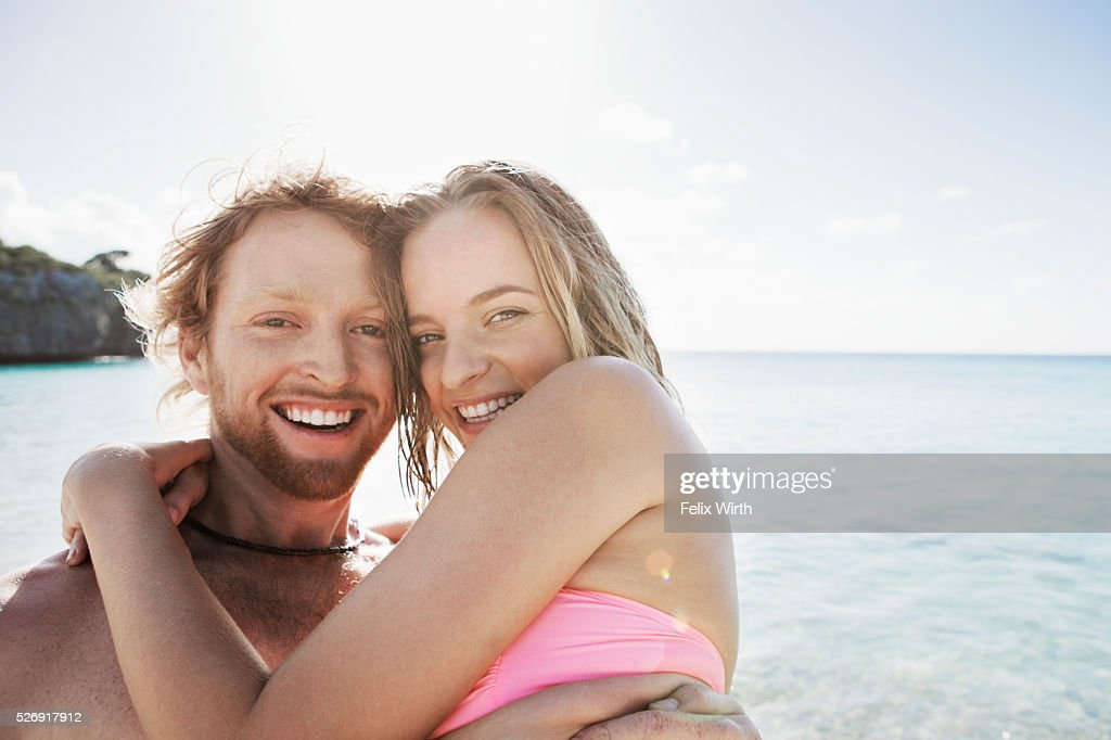 Young couple embracing on sea shore : Stock Photo