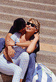 Young couple embracing on steps, man kissing woman on neck