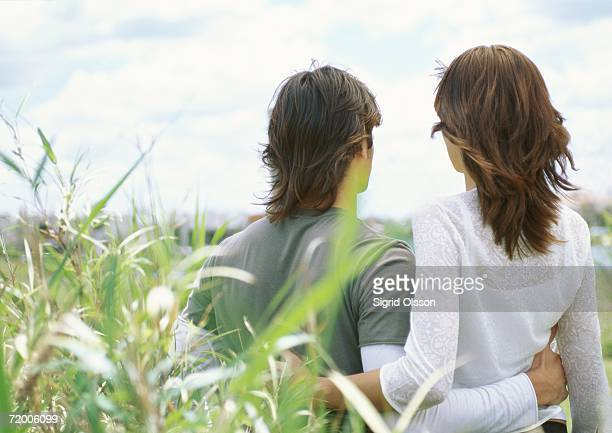 Young couple embracing outdoors, rear view