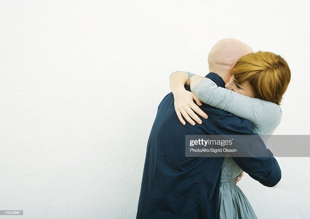 Young couple embracing, side view