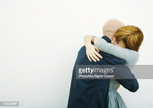 young couple embracing side view stock foto getty images. Black Bedroom Furniture Sets. Home Design Ideas