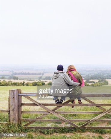 Young couple embracing, sitting on fence by field, rear view : Stock Photo