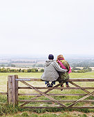 Young couple embracing, sitting on fence by field, rear view