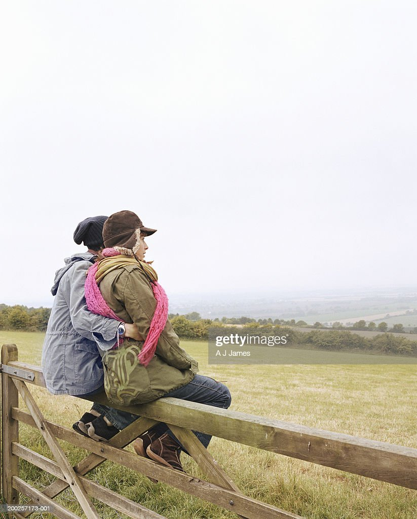 Young couple embracing, sitting on wooden fence by field : Stock Photo