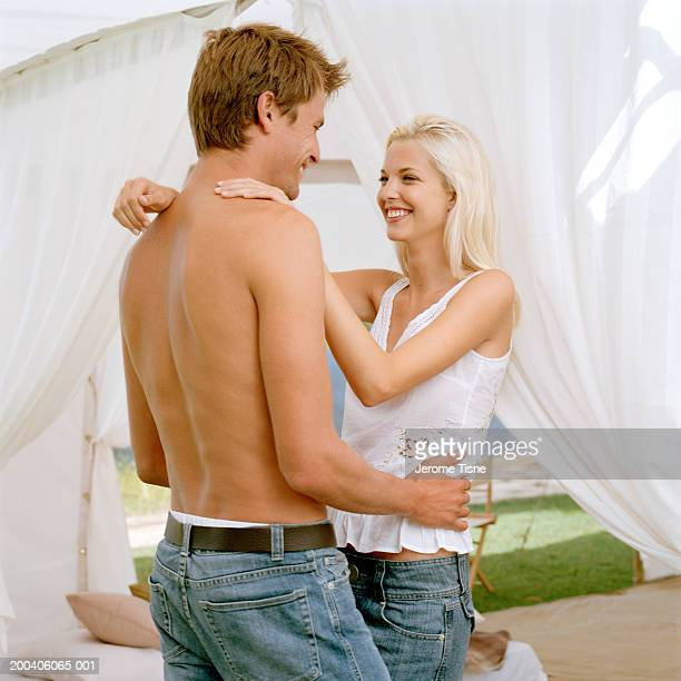 Young couple embracing under tent, smiling, side view