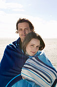 Young couple embracing, wrapped in blanket on beach, portrait