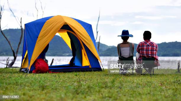 Young couple enjoy Camping Outdoors , sky cleared in background . Holiday , vacation , summer concept .