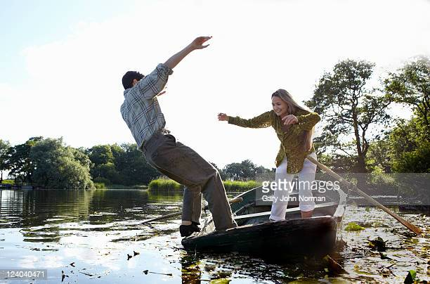 Young couple enjoy playful rowing on river