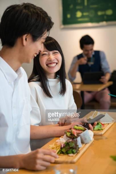 Pareja joven disfrutando de una almuerzo informal fecha juntos en un café