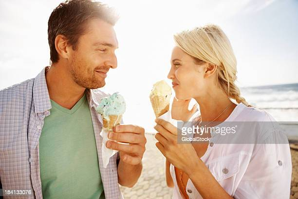 Young couple enjoying an ice cream on the beach