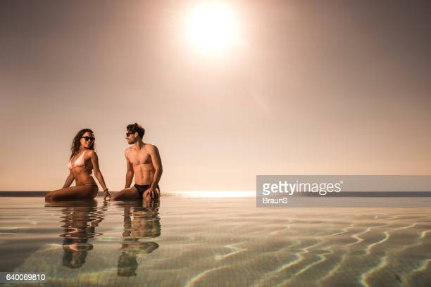Young couple enjoying in summer day at infinity pool.