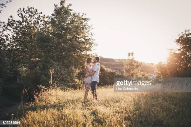 A young couple enjoying leisure outdoors in a romantic sunset.