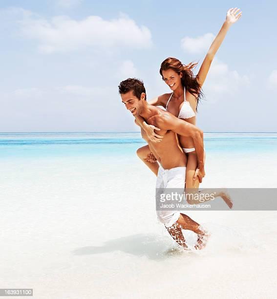 Young couple enjoying piggy back ride on beach