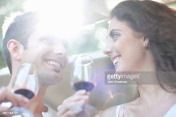 Young couple enjoying wine tasting at vineyard