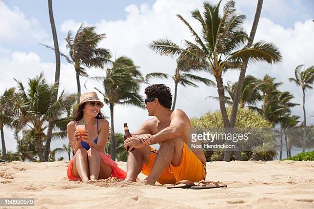 A young couple enjoys drinks on the beach