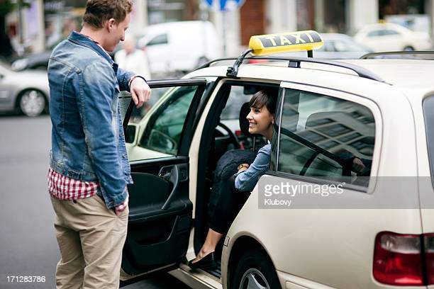 Young couple entering the taxi cab