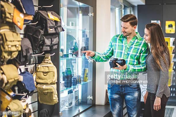 Young couple examining camera lenses
