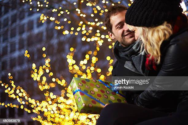 Young couple exchanging gifts next to outdoor xmas lights