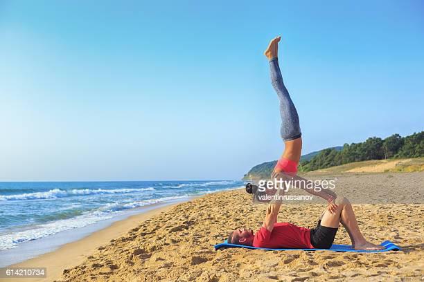 Young couple exercising acroyoga on beach