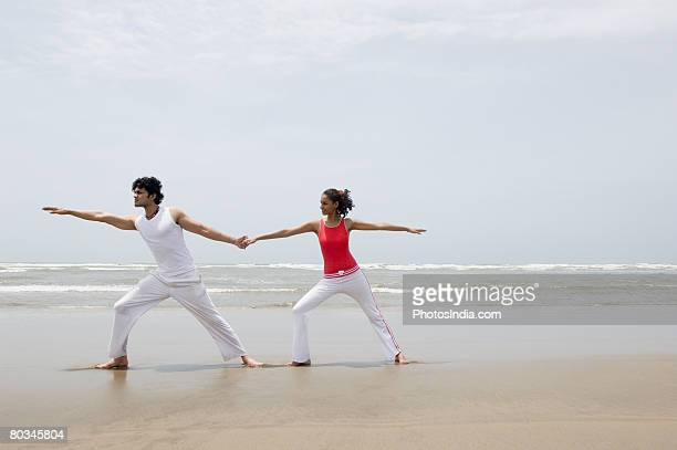 Young couple exercising on the beach