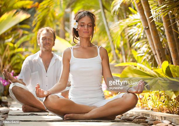 Young couple exercising yoga surrounded by tropical greenery.