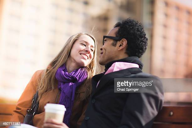 Young couple face to face on park bench, New York, USA