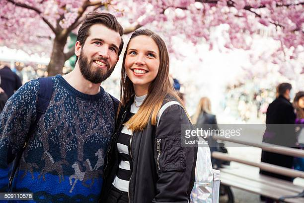 Young couple fall in love under a beautiful cherry tree