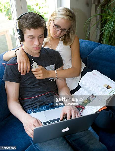 Young couple female and male with textbook laptop smartphone and headphones on a sofa