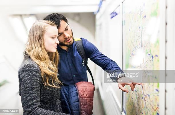 Jeune Couple à la recherche de leur chemin dans la station de métro
