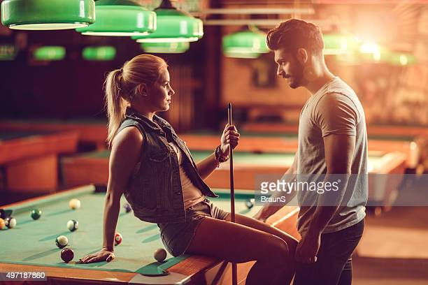 Young couple flirting during a pool game in a pub.