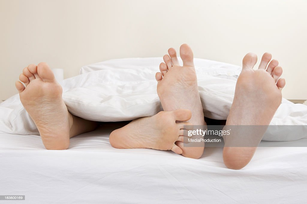 Young couple flirting in bed : Stock Photo