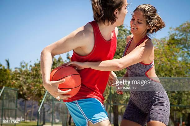 Young couple flirting on basketball court