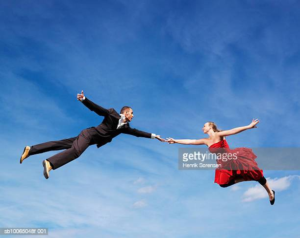Young couple flying in air, low angle view