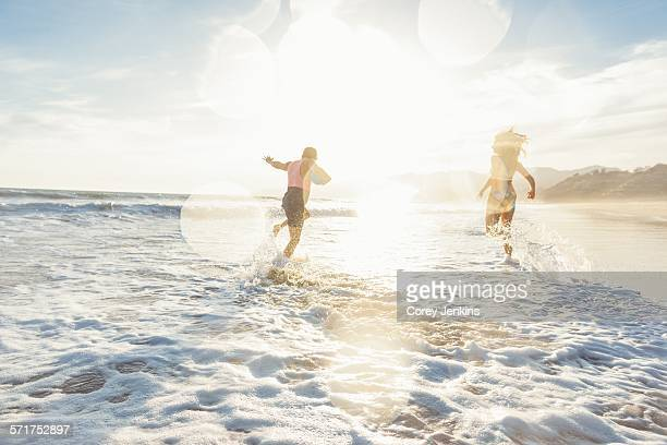 Young couple fooling around on beach, on sea, sunset