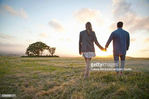 Young couple gazing at sunset in rural field, Dorset, England